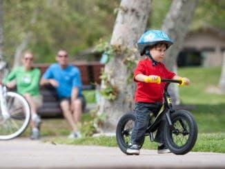 Ребенок учится кататься на двухколесном велосипеде