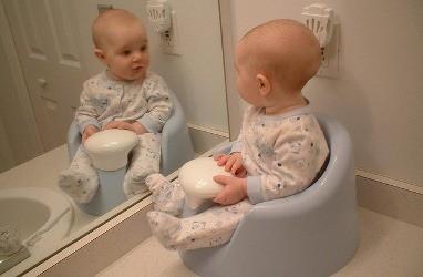 Ребенок смотрит свое отражение в зеркале